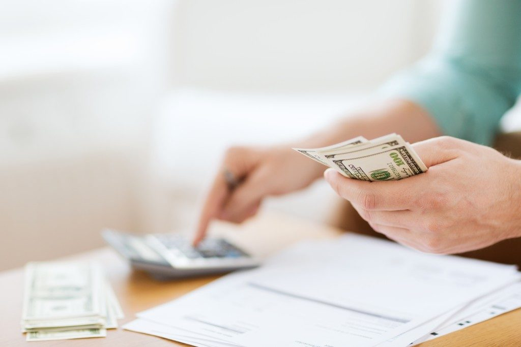 man holding money calculating the financial responsibiilities that needed to be settled