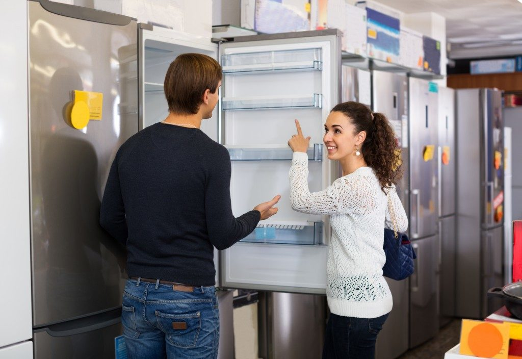 man and woman looking at appliances