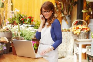 flower shop owner taking order via phone and logging it into the file in the laptop