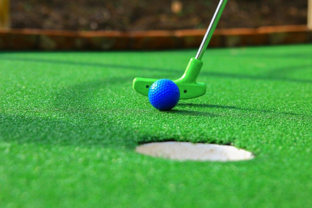 playing golf in an artificial grass golf area