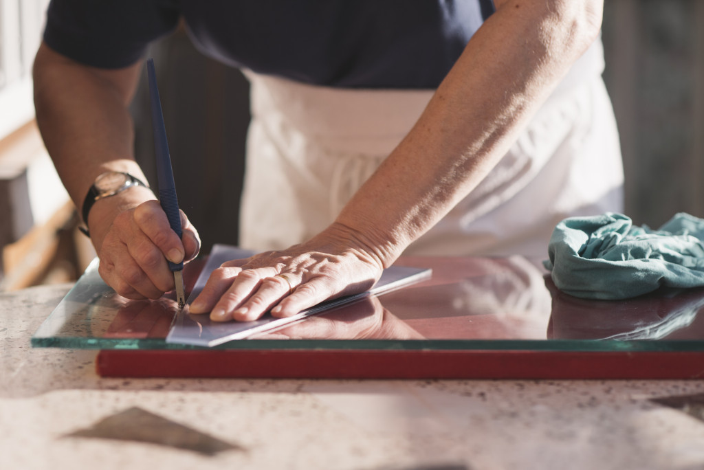 man cutting glass